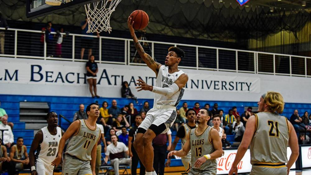 A Sailfish men's basketball player glides to the hoop.